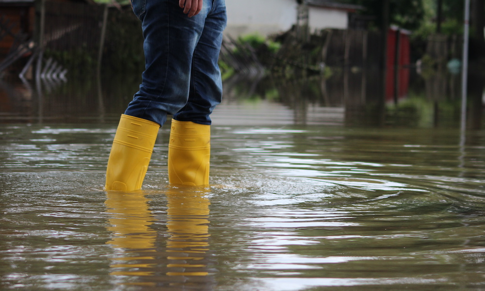 Blog - Person-Standing-In-High-Water-Wearing-Yellow-Rain-Boots-And-Jeans